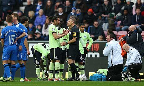 Massadio Haidara reels in pain following a challenge from Wigan's Callum McManaman